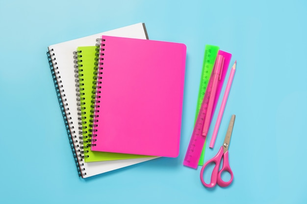 Colorful girlish school supplies, notebooks and pens on punchy blue. top view, flat lay. copy space. Premium Photo