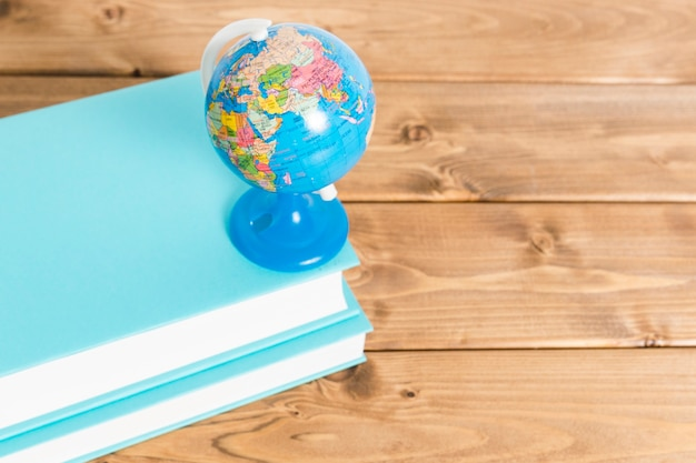 Colorful globe on blue books on wooden table Free Photo