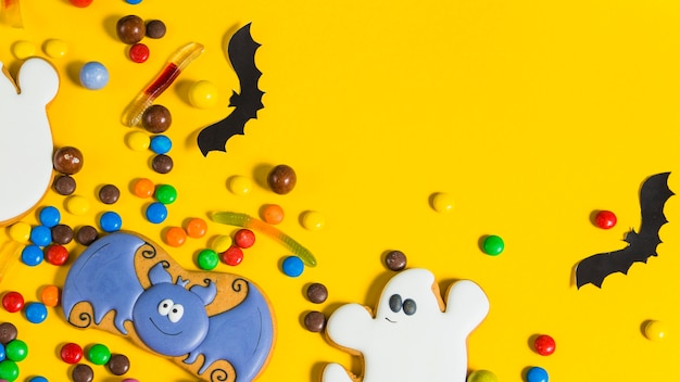 Colorfulhalloween candies and paper bats Free Photo
