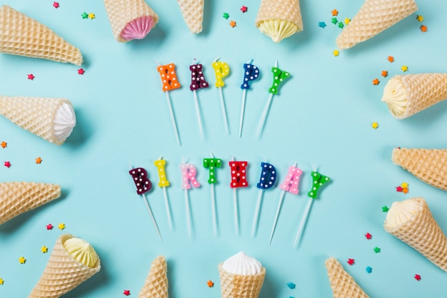 Colorful happy birthday candles decorated with aalaw in waffle cones on blue backdrop Free Photo