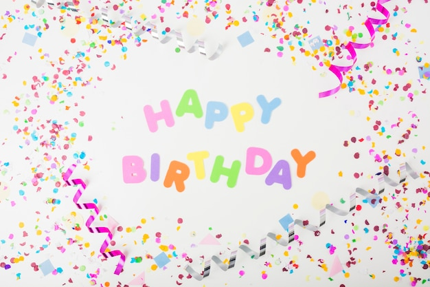 Colorful happy birthday text with confetti and curling streamers on white background Free Photo