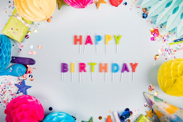 Colorful happy birthday with decorative items on white background Free Photo