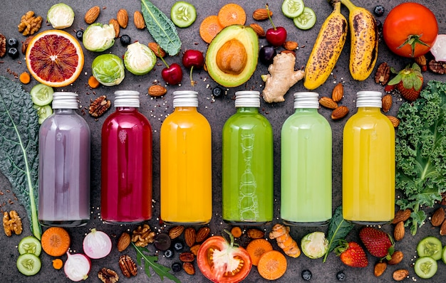 Colorful healthy smoothies and juices in bottles with fresh tropical fruit and superfoods on dark stone Premium Photo