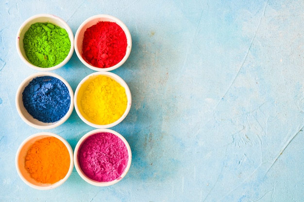 Colorful holi color powder inside the white bowls on painted blue backdrop Free Photo