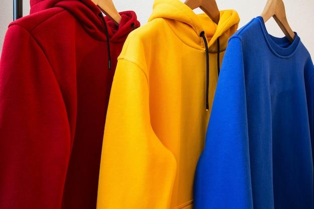 Colorful hoodies on hangers close-up modern design Premium Photo