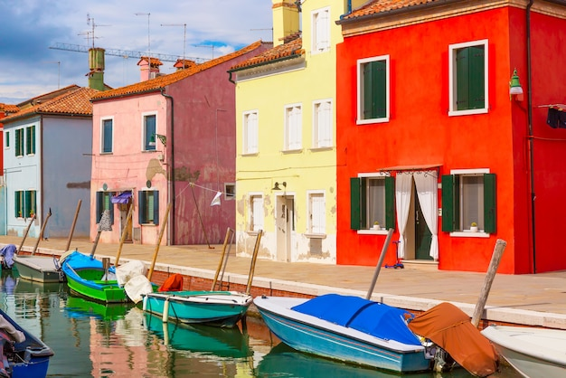 Colorful houses and boats in burano island with cloudy blue sky near venice, italy, Premium Photo