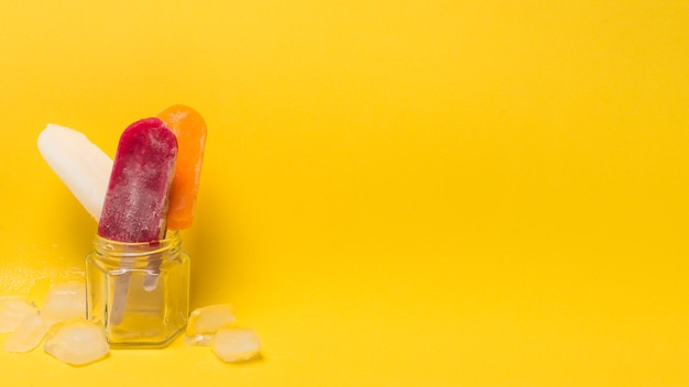 Colorful ice lolly in jar near ice Free Photo