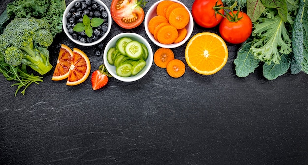 Colorful ingredients for healthy smoothies and juices on dark stone Premium Photo