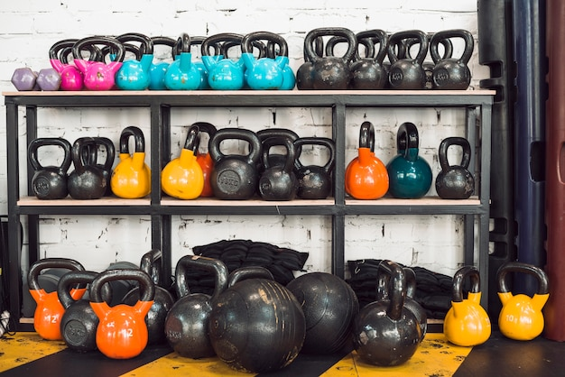 Colorful kettlebells arranged in rack | Free Photo