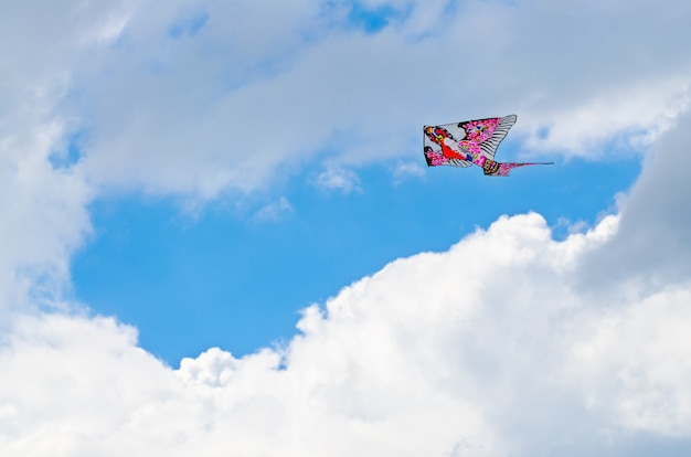 Colorful kite in the blue sky with a big cloud Premium Photo