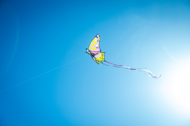 Colorful kite with long tail flying in the blue sky against the sun Premium Photo
