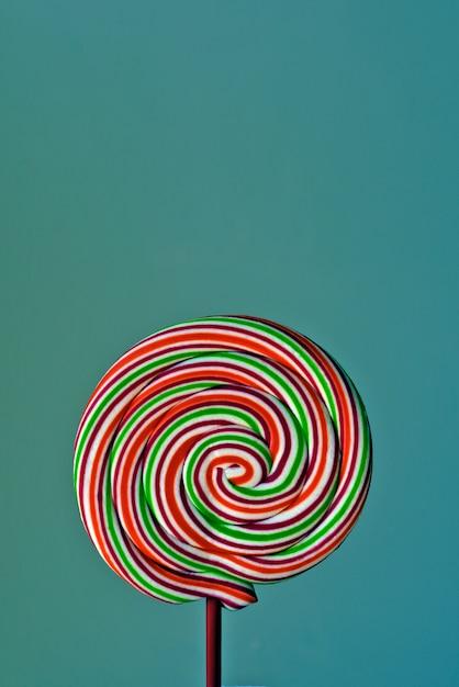 Красочный леденец в форме спирали на зеленом фоне Premium Фотографии