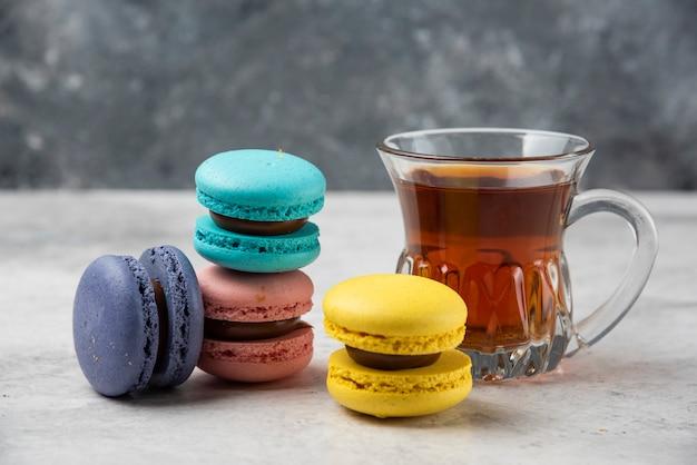 Красочные macarons с чашкой черного чая на белом столе. Бесплатные Фотографии