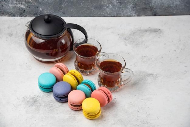 Красочные macarons с чашкой и двумя чашками черного чая на белой поверхности. Бесплатные Фотографии