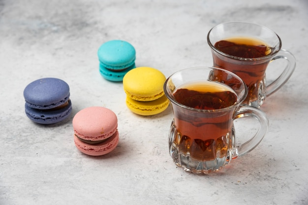 Красочные macarons с двумя чашками черного чая на белой поверхности. Бесплатные Фотографии