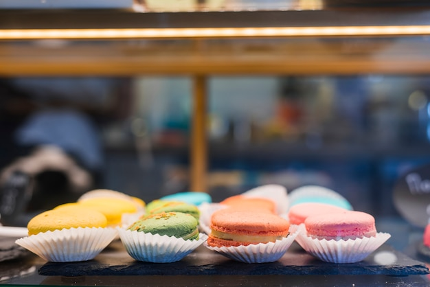 Colorful macaroons in the cupcake paper holder inside the display cabinet Free Photo