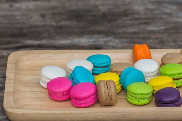 Colorful macaroons in dish on wooden table Premium Photo