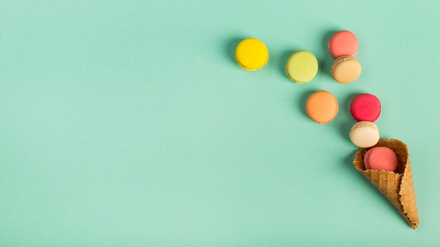 Colorful macaroons spilling from the waffle cone on mint green backdrop Premium Photo