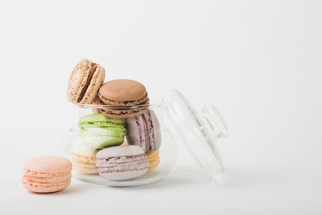 Colorful macaroons in transparent open glass jar on white backdrop Free Photo