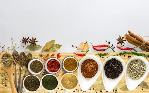 Colorful of many spices and herbs on white little bowl and spoons put on wood plank Premium Photo