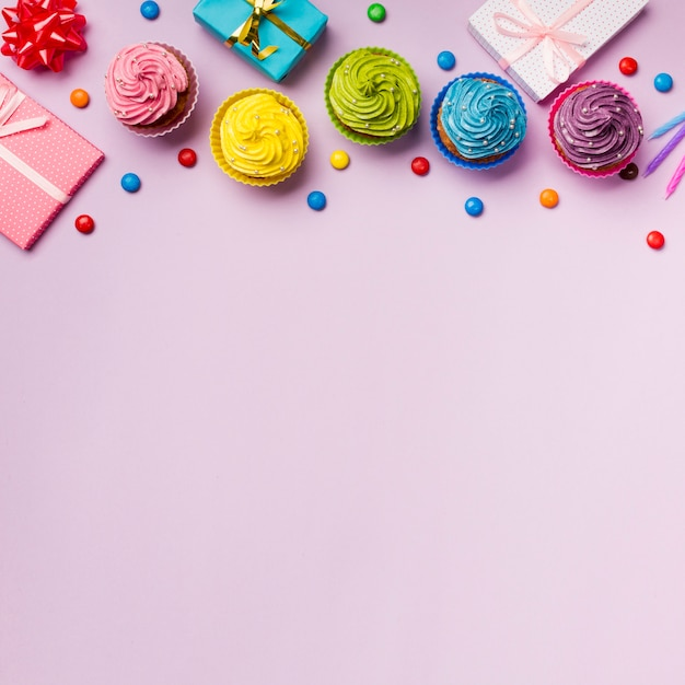 Colorful muffins and gems with wrapped gift boxes on pink backdrop Free Photo