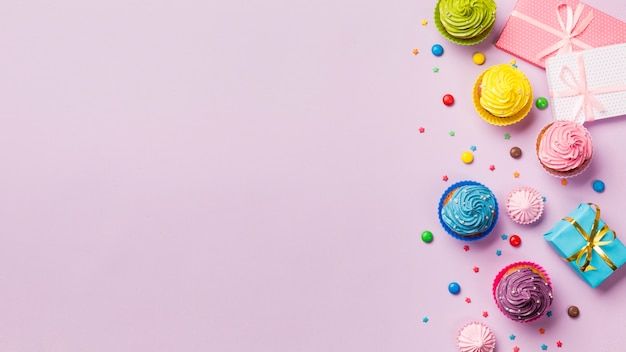 Colorful muffins and gems with wrapped gift boxes with copy space on pink backdrop Free Photo