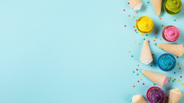 Colorful muffins with aalaw waffle cones and sprinkles on blue background Free Photo