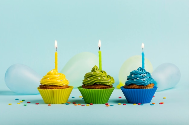 Colorful muffins with candles; sprinkles and balloons on blue backdrop Free Photo