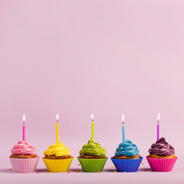 Colorful muffins with lighted candles in a row with sprinkles on pink backdrop Free Photo