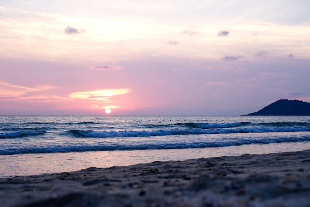 Colorful ocean beach sunset with deep orange blue sky and sun rays. Premium Photo