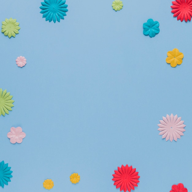 Colorful origami flowers cutout on blue background Free Photo