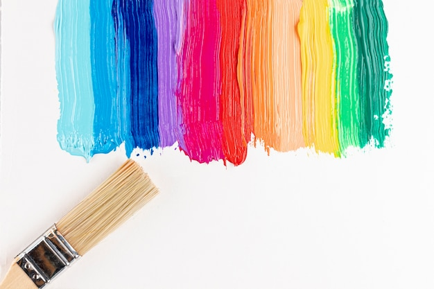 Colorful paint strokes and brush Free Photo