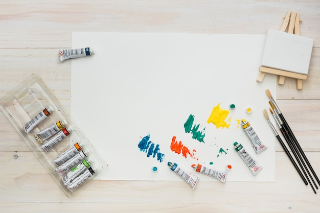 Colorful paint tube colors on white sheet with mini easel and brushes Free Photo
