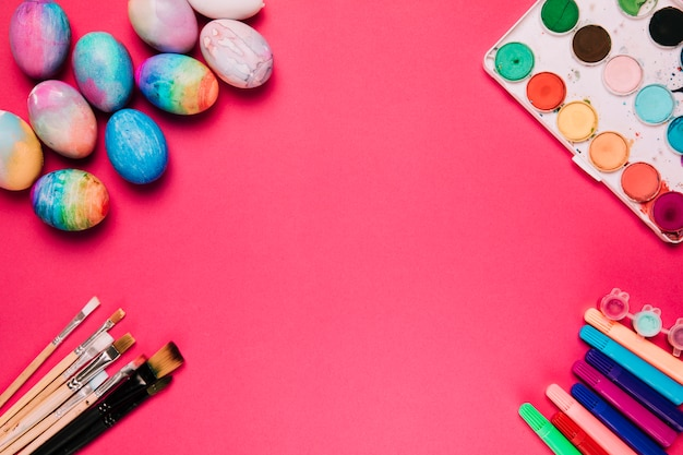 Colorful painted easter eggs; paint brushes; paint box and felt tip pen on pink background Free Photo