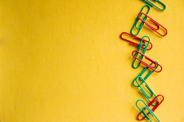 노란색 배경에 고립 된 다채로운 종이 클립 프리미엄 사진