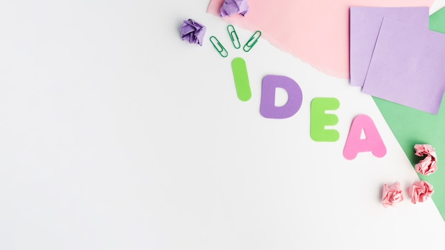 Colorful paper cutout of idea text letter and paperclip with crumpled paper Free Photo