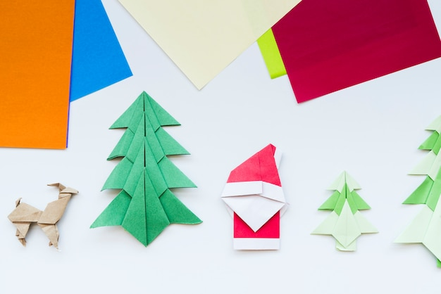 Colorful paper and handmade christmas tree; reindeer; santa claus paper origami isolated on white backdrop Free Photo