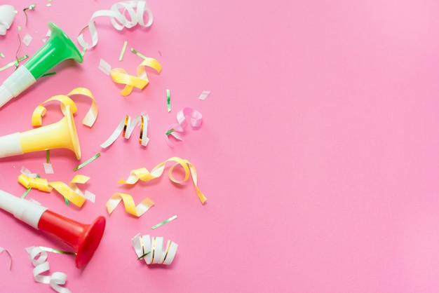 Colorful party streamers on pink background. Premium Photo