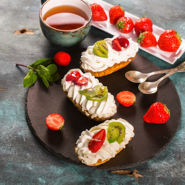 Colorful pastry cakes with chantilly cream, fruits and berries on grunge blue wooden background Premium Photo