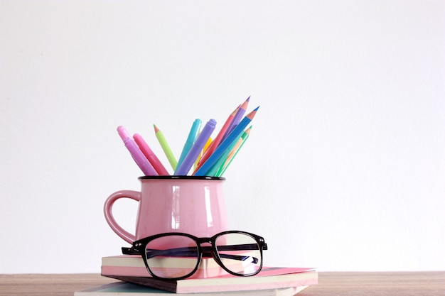 Colorful pencil color and marker on top of books and glass Premium Photo