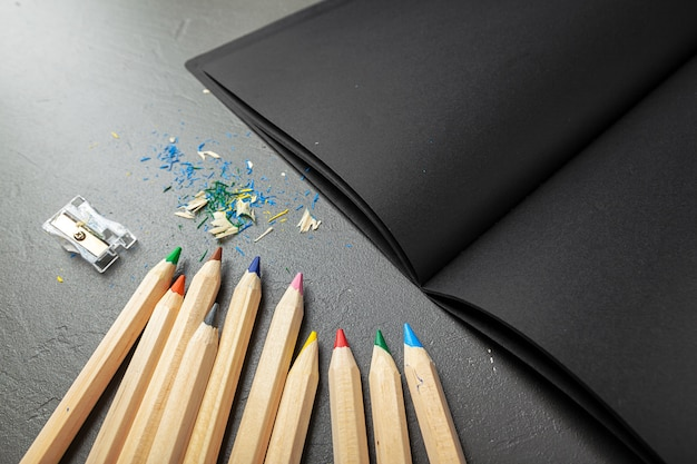 Colorful pencils and black book Premium Photo