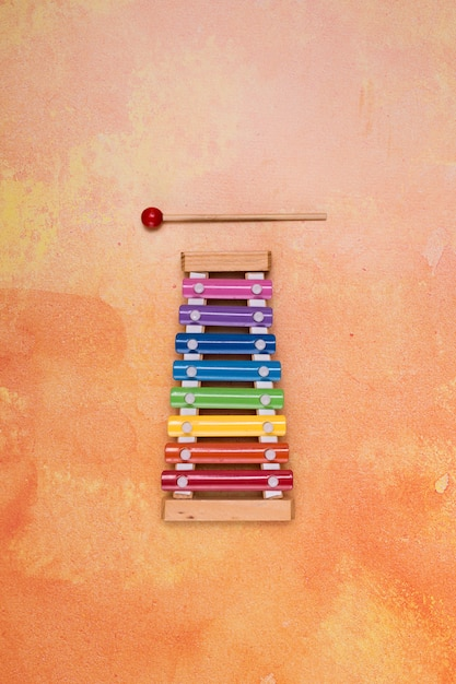 Colorful piano for kids on orange background Free Photo