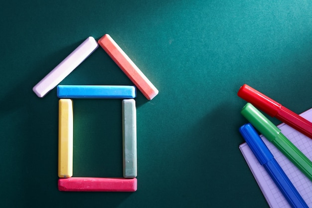 Colorful pieces of chalk put in form of house on blackboard Free Photo
