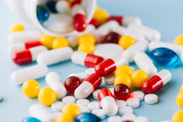 Colorful pills and plastic bottle Free Photo