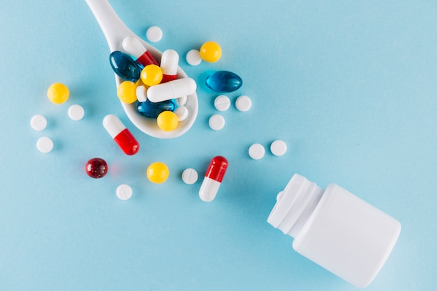 Colorful pills on spoon Free Photo