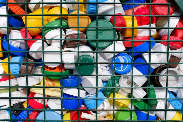 Colorful plastic bottle caps behind iron bars  concept
