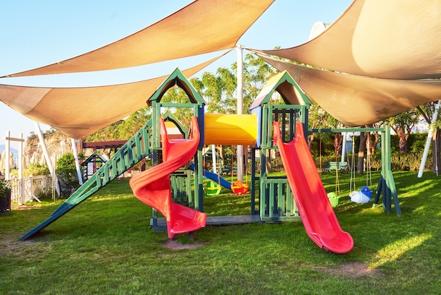 Colorful playground in the yard in the park at sunset. Free Photo