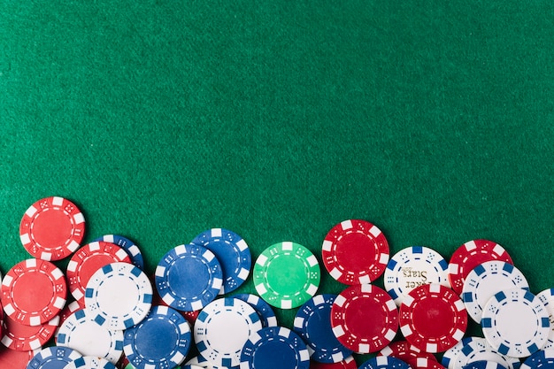 Colorful poker chips on green background Free Photo
