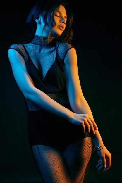 スタジオで黒にポーズをとってセクシーなファッションドレスで官能的な美しいブルネットの女性のカラフルな肖像画 Premium写真