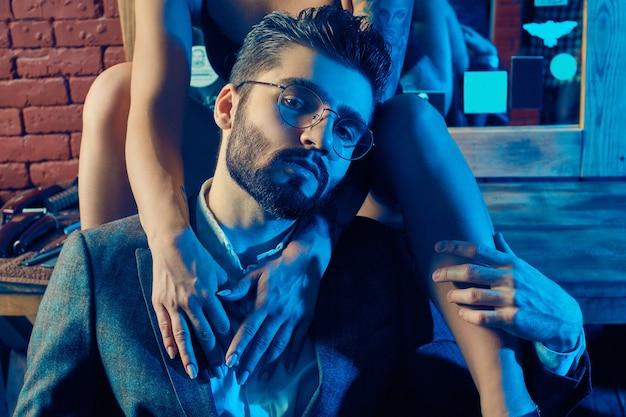 Красочный портрет красивой пары: брутальный мужчина в элегантном костюме и сексуальная девушка с татуировкой в нижнем белье в парикмахерской Premium Фотографии